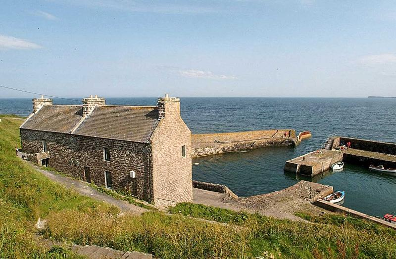 View of the house and harbour, looking across the sea