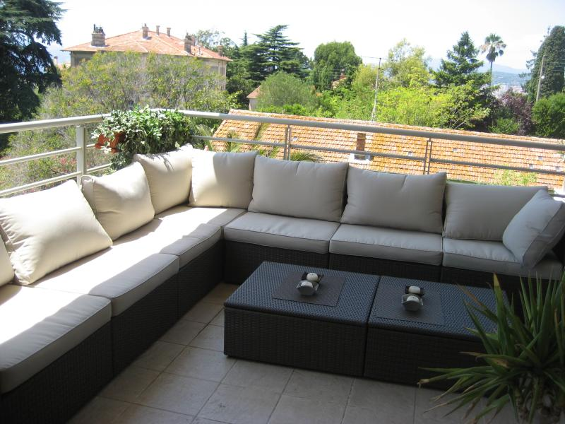 Relax on contempory balcony sofas. A view of the sea through the trees.