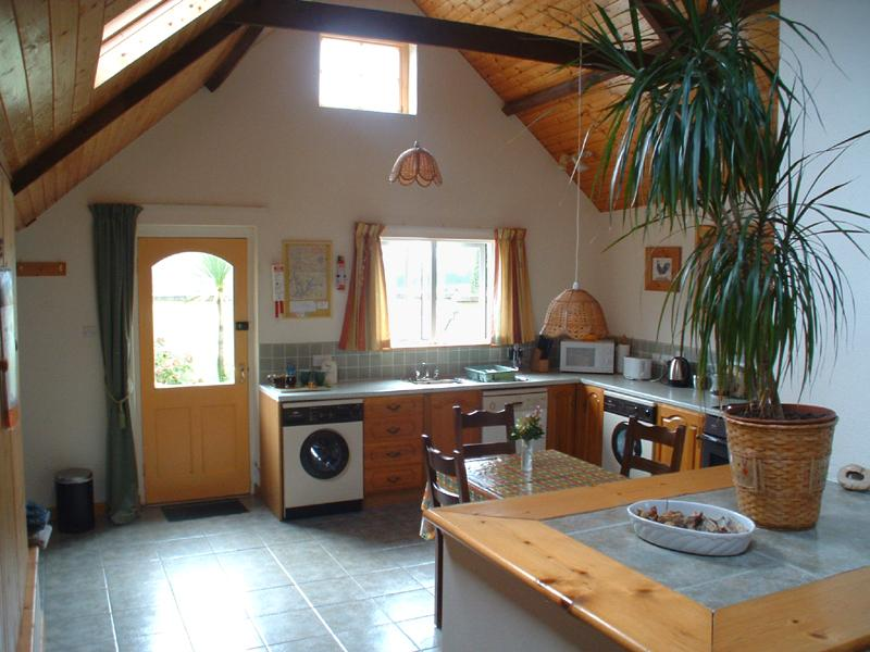 Horseshoe Cottage's well equipped kitchen has high beamed ceiling and opens onto a private pati