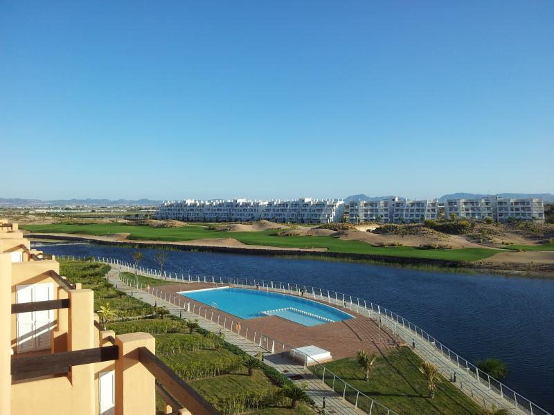 The view from the terrace to the pool, lake and golf course.