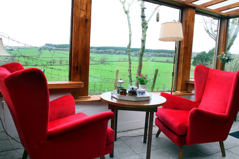 Conservatory with views across the rolling green valley.