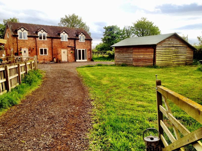 Approach to the barn with ample parking and view of the wooden playden