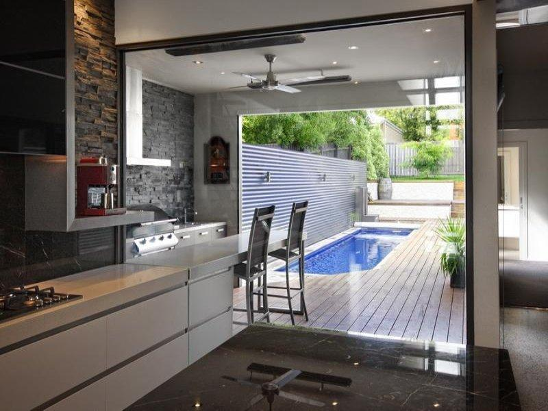 Three indoor living zones in this modern house, led onto an outdoor kitchen/barbeque and pool area.