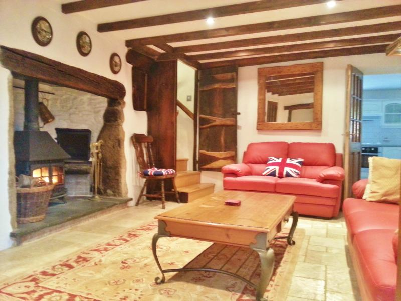 Main reception room with natural stone floor and original Cornish granite fire place.