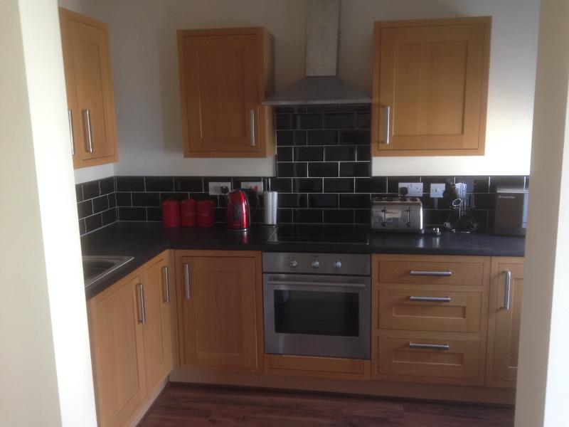 newly fitted kitchen with oven, hob, microwave, toaster, kettle, washing machine, fridge freezer