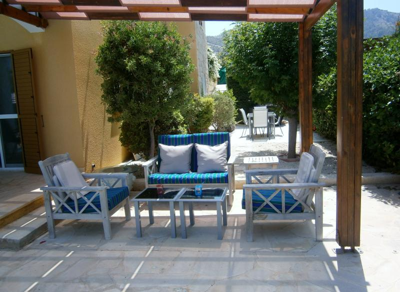 Shaded seating area by the pool with private dining area and barbeque behind