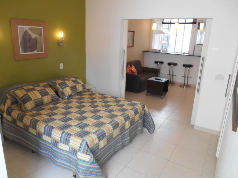 Queen size bed and double doors to living/kitchen area