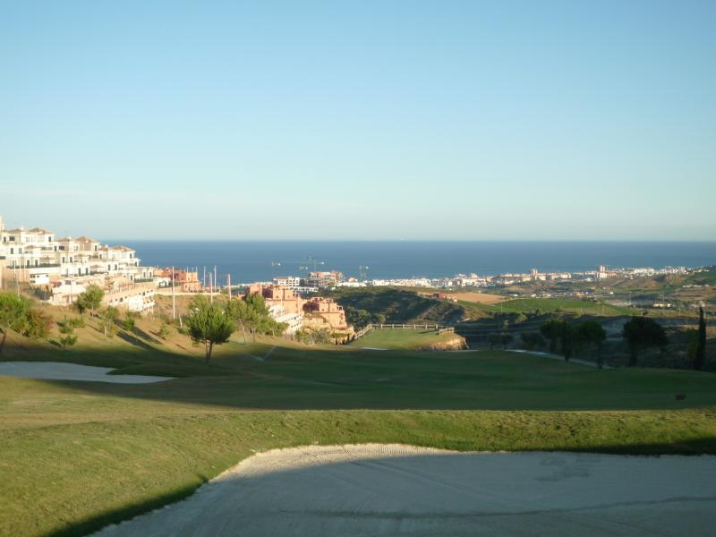 Stunning view over golf course down to the sea from garden terrace.