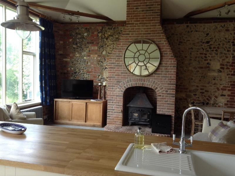 Spacious open plan sitting room with wood burning stove