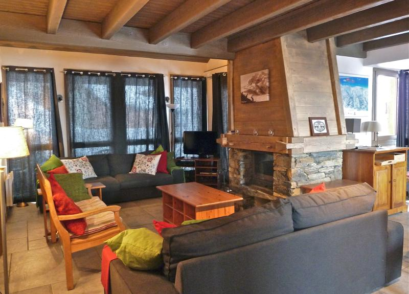 Living area with log fire, LCD TV and double doors leading to large balcony overlooking the piste
