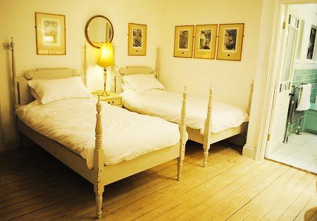 Newly refurbished twin bedroom with limed oak floor and gas central heating original art on walls.