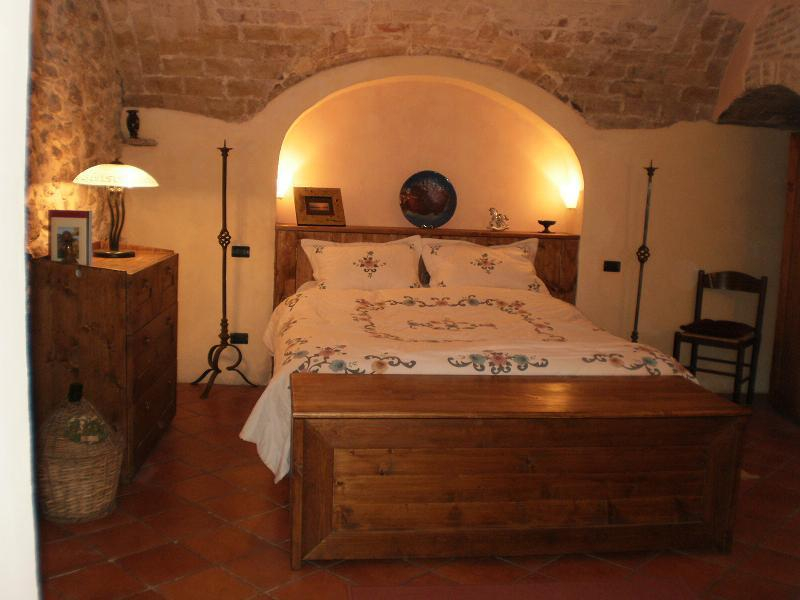 The bedroom is full of character and rustic charm with a curved ceiling and exposed stone walls.