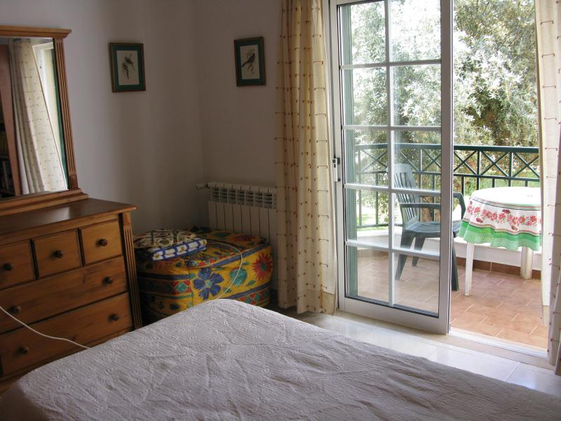 Second bedroom with a single bed, pull-up bed and a terrace overlooking garden.