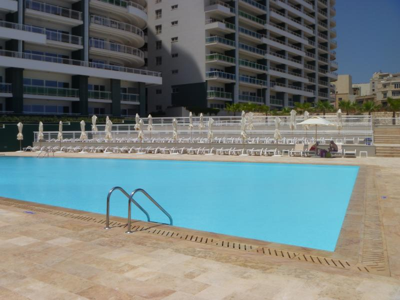 swimming pool with sunbeds and umbrellas provided