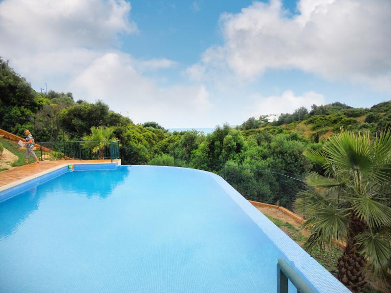Large infinity pool, surrounded by countryside and views of the sea
