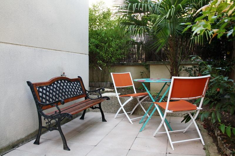 Patio table, two chairs and a bench with the sun