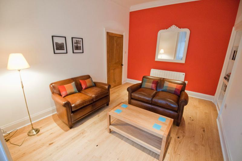 Livingroom beautifully furnished with leather sofas, oak furniture and silk soft furnishings.