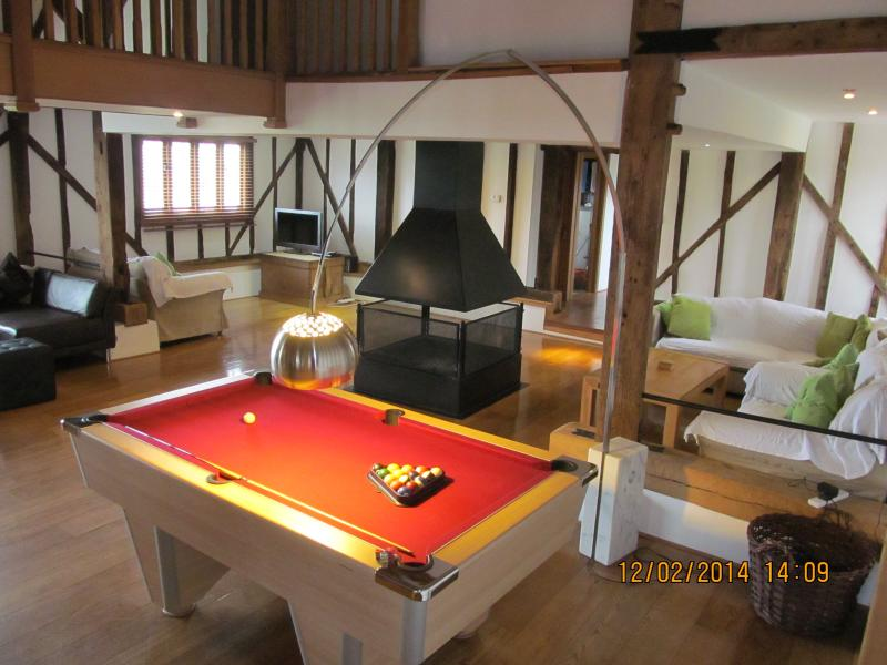 pool table in sitting room, with open fire pit in the middle.