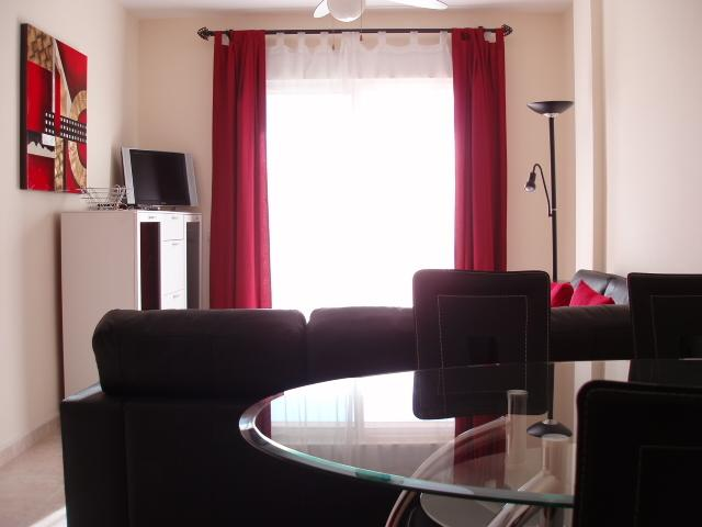 The view from the dining end of the open plan living area, with TV, DVD player, leather corner unit.