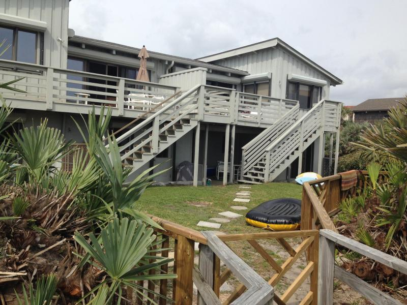 The back deck has a view of the ocean and overlooks the back yard which has a wooden fence
