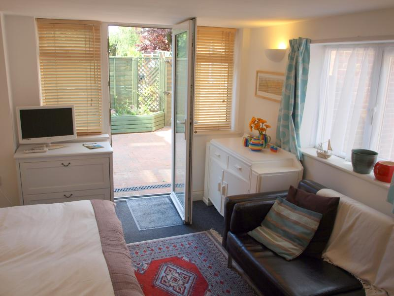 View from dining area: Double bed, 3-seater sofa, Freeview TV/DVD and door open to sunny private cou