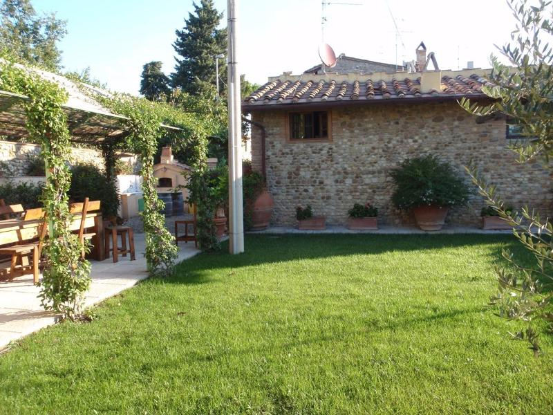 Private garden with luxury dining and lounge furniture and pizza oven