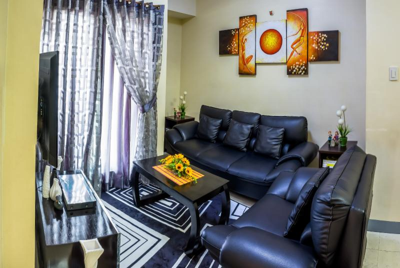 Cozy and comfy living room with a 46 inch TV, a leather sofa, nice carpet, and decorations