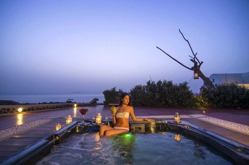 Outdoor private heated hydromassage spa with endless view in front of the sunset of Oia.