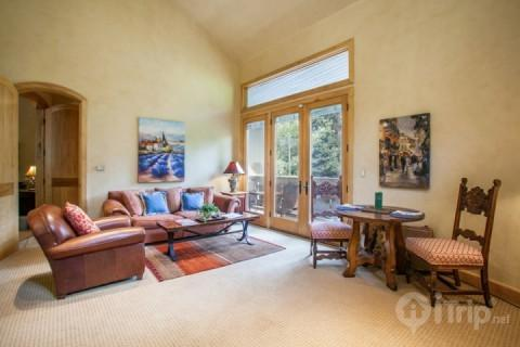 Beautiful European style living room, french doors opening to scenic Gore Creek and dining table for 2.