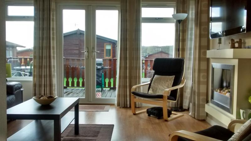 Bright and airy spacious open plan lounge.Patio doors open onto a large wraparound decking area