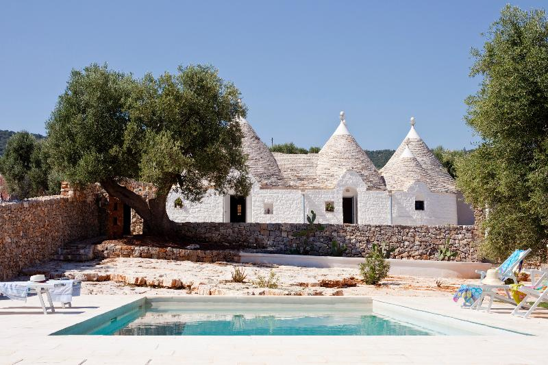 Cluster of 300-year old trulli surrounded by olive trees
