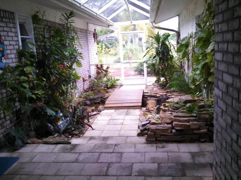 Lanai entrance with foot bridge, fish pond & waterfall