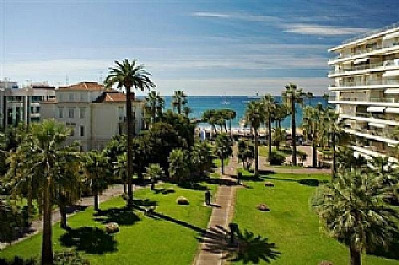 Beautiful view of the gardens of the grand hotel. Well decorated in a summer fashion with grass, palm trees and the fantastic blue sea in the background.