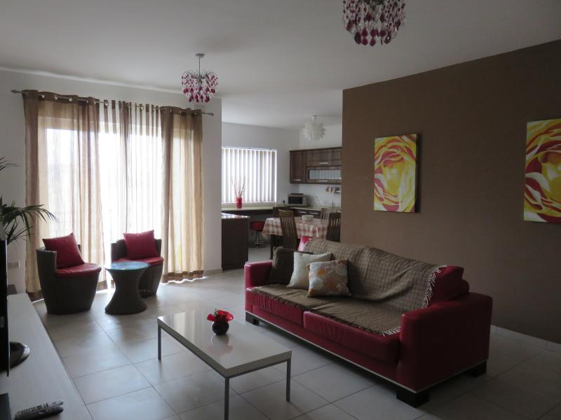 Livingroom area with front balcony,AC and kitchen area