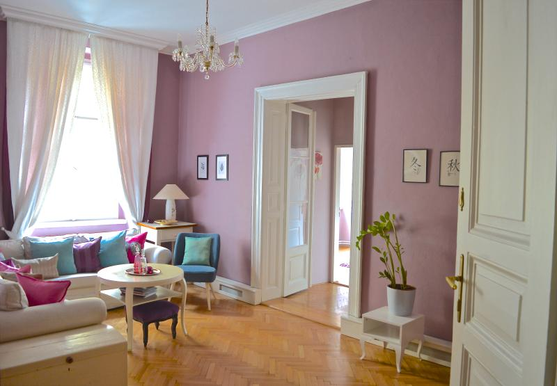 Sunny living room with original parquet floors, restored French doors to bedroom.