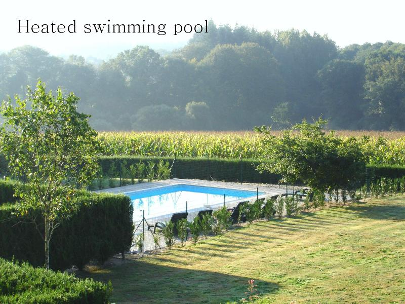 Heated swimming pool next to open countryside