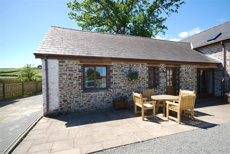 Dan-y-Coed is a single storey stone cottage at one end of a group of three, with patio furniture to the front