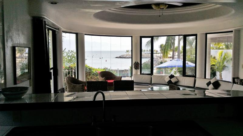Standing in kitchen overlooking dining, living, private pool and direct beachfront