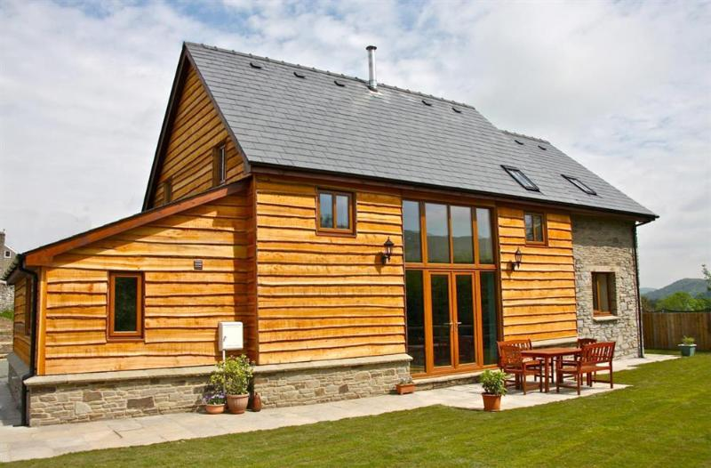 This attractive stone and timber-clad detached barn conversion has lawned gardens, patio and garden furniture