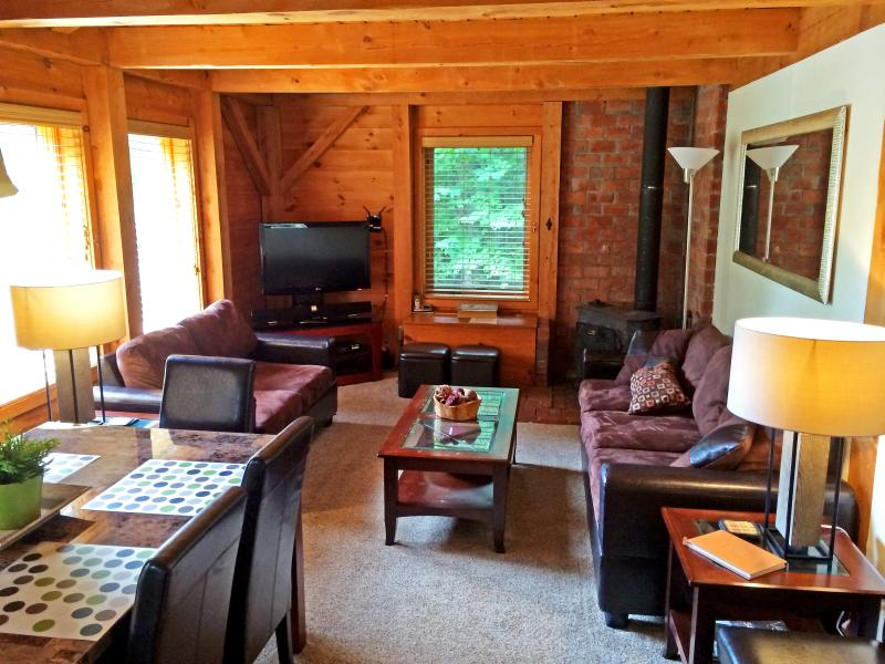 Left Unit: Cozy living and dining room with a wood burning stove and firewood.
