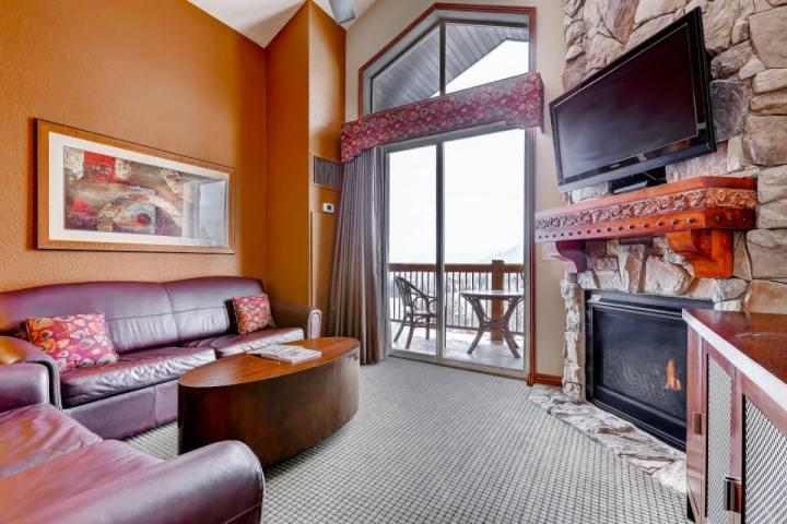 Spacious and comfortable living room with queen size sleeper sofa, stone fireplace, private balcony and 42' HDTV.