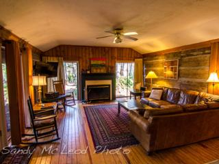 Living room with log walls and wood burning fireplace. And we provide the wood in season.