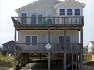 Exterior of home from the beach road shows open and covered porches as well as hot tub room
