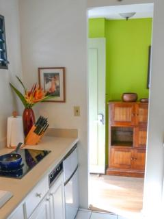 Galley kitchen with refrigerator, microwave, coffee maker and dishes and glassware