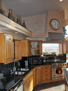 Black granite counter tops and cherry wood cabinetry