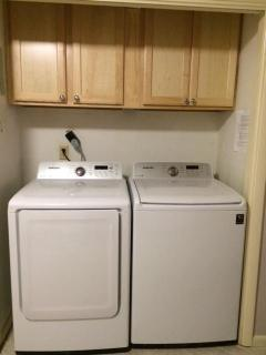Laundry area with new high efficiency washer and dryer.