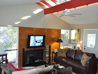 Living and dining have lots of light from clear story windows and large floor to ceiling window