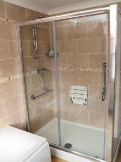 large walk in shower with seat and hand rails