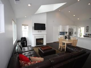 Bright and ample living room with fireplace and vaulted ceilings.