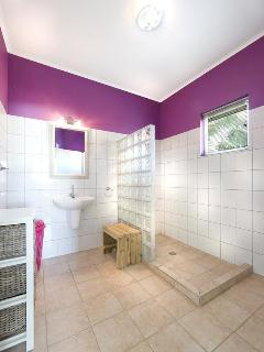 Private bathroom with purple bedroom